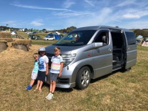 campervan in a field with happy kids