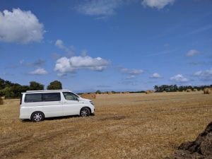 Campervan in a field with hay bales